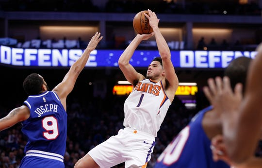 Suns guard Devin Booker shoots over Kings guard Cory Joseph during a game Nov. 19.