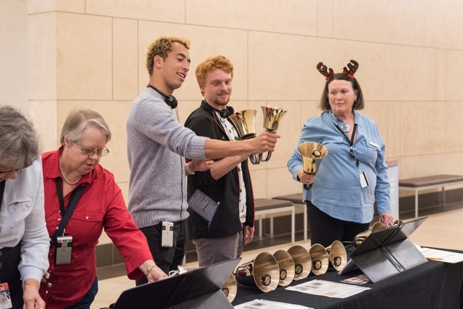 Visitors experiment with handbells at MIM's 2018 'Tis the Season holiday event.