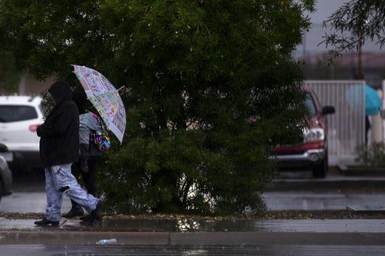 People walk in the rain near Glendale High School on Nov. 20, 2019, in Glendale.
