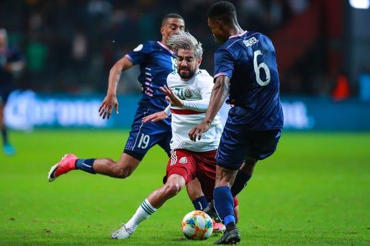 Rodolfo Pizarro intenta eludir la marca de dos jugadores de Bermudas.
