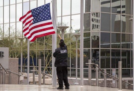 Valentino Fuentes, guardia de seguridad de Chase, baja la bandera durante la tormenta que azota el centro de Phoenix.