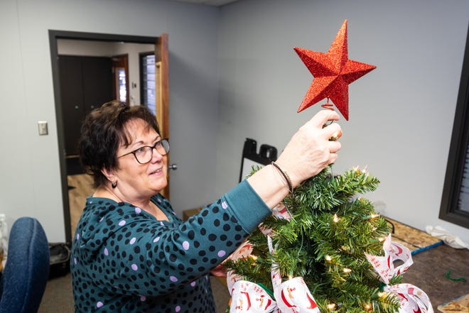 Festival of Trees committee member and volunteer Deb Callahan puts a star on top of a Christmas tree Wednesday, Nov. 20, 2019, in the McLaren Port Huron Foundation's office in Port Huron.