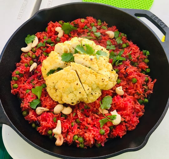 Whole roasted cauliflower sits on a colorful bed of rice with beets and green peas in this recipe by Rinku Bhattacharya.