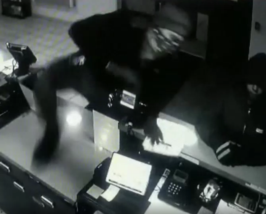 A man hurdles the desk at the Motel 6 in Manchester Township on Sunday during a robbery.