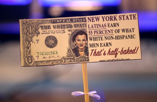 This re-creation of a dollar bill shows the pay inequity of Latina women compared to white men.