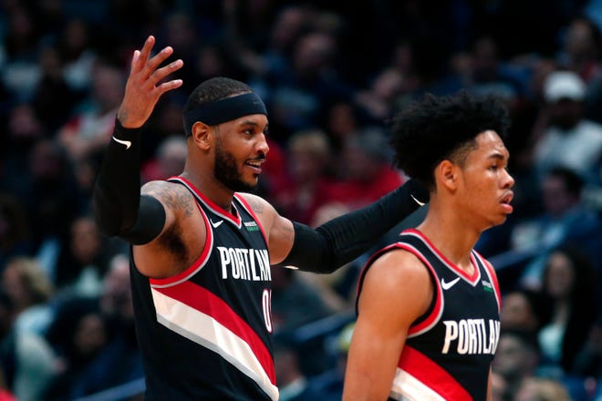 Portland Trail Blazers forward Carmelo Anthony, left, reacts as he walks to the bench with guard Anfernee Simons during the second half of the team's NBA basketball game against the New Orleans Pelicans in New Orleans, Tuesday, Nov. 19, 2019. The Pelicans won 115-104.