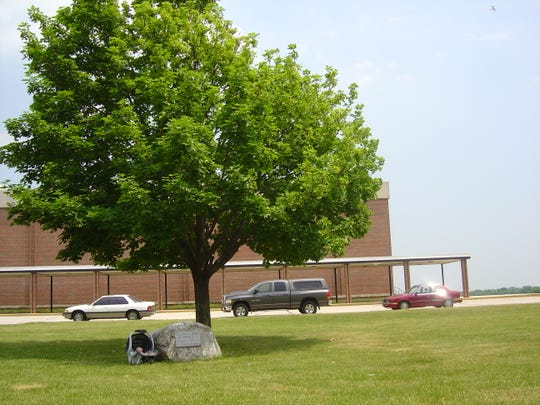 Mike Steinke's son Bradley Steinke sits near the memorial tree outside of Plymouth High School in 2005. Steinke named his son after his best friend Brad Johnson, who was killed in a train accident in 1984, along with his sister Lisa Johnson. The class of 1985 created the memorial to remember them shortly after.