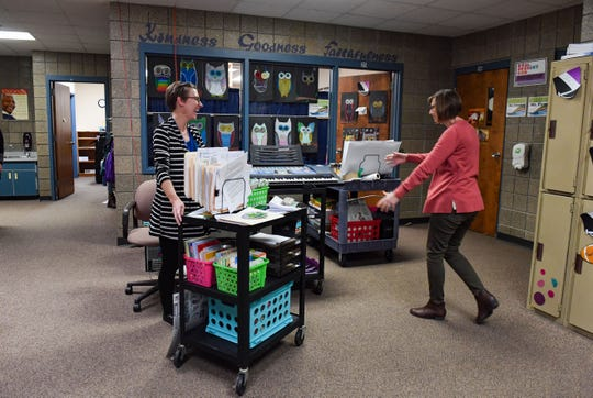 Spanish teacher Melinda Wood and music teacher Karen Dooley grab their respective class carts from the hallway between class periods on Wednesday, Nov. 20, at Sioux Falls Lutheran School. Spanish, music and art classes have been reduced to fit on rolling carts that travel between classrooms in order to conserve space.