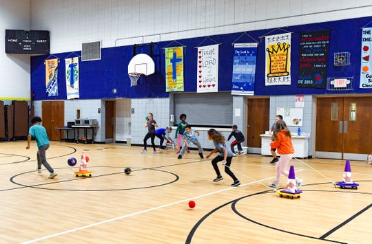 Students run past closed-up lunchroom equipment and auditorium tapestries while playing a game during physical education class on Wednesday, Nov. 20, at Sioux Falls Lutheran School. The space used as a gymnasium also fills the role of cafeteria and auditorium.