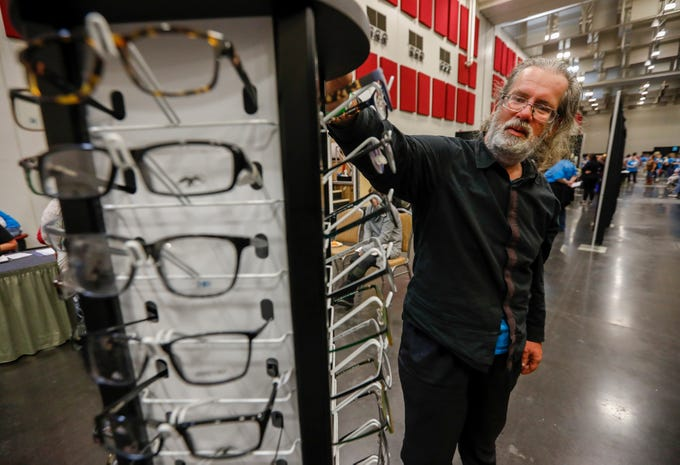 Gary Hamilton looks for a new pair of glasses during the Hope Connection event at the Springfield Expo Center on Wednesday, Nov. 20, 2019. Hope Connection is a one-day, one-stop service site for the Ozarks' homeless and poverty stricken to gain access to vital services.
