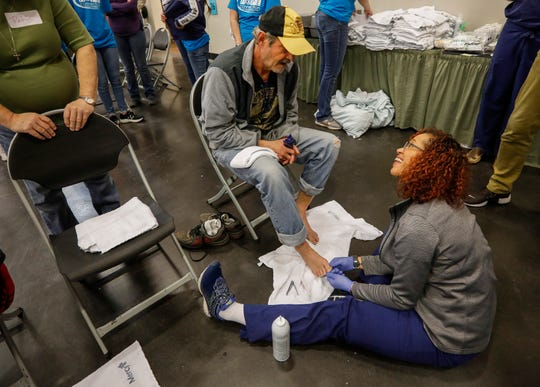 Bjai Rice, right, a medical resident in the Cox Family Medicine Residency Program, examines Keith Tedder's feet during the Hope Connection event at the Springfield Expo Center on Wednesday, Nov. 20, 2019. Hope Connection is a one-day, one-stop service site for the Ozarks' homeless and poverty stricken to gain access to vital services.
