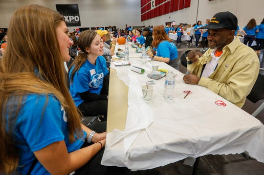 Darnell Patrick, right, talks with volunteers Kayla Kroeger, left, and Nicole Lehman during the Hope Connection event at the Springfield Expo Center on Wednesday, Nov. 20, 2019. Hope Connection is a one-day, one-stop service site for the Ozarks' homeless and poverty stricken to gain access to vital services.