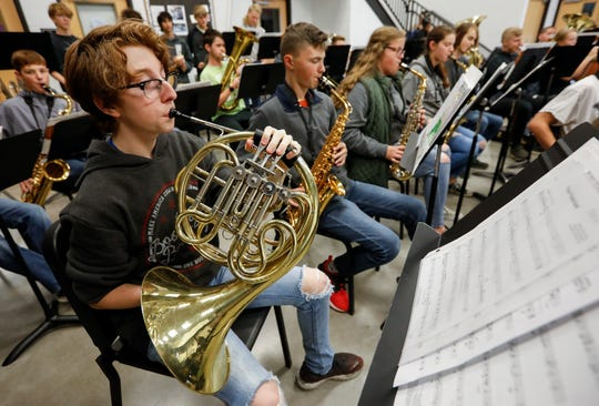 Brock Smith plays the French horn while rehearsing Christmas songs with the concert band at Sparta High School on Monday, Nov. 18, 2019.