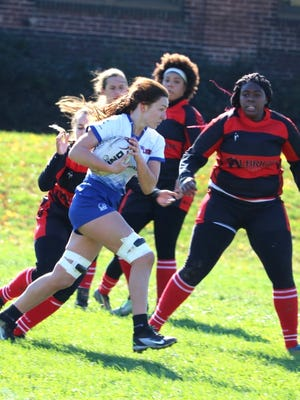 Ginger Gibbons, who has the ball, is part of the rugby team at Lee University in Cleveland, Tennessee.