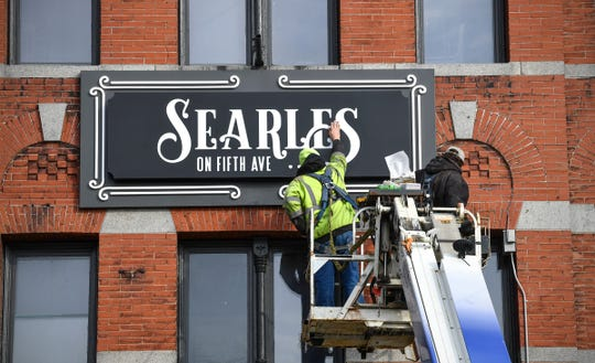 Ben Arneson and Adrion Jennen of Indigo Signworks put the finishing touches on a newly-installed sign for Searle on Fifth Ave. Wednesday, Nov. 20, 2019, in St. Cloud.