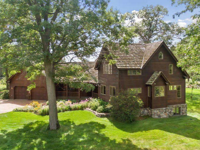The approach to this five-bedroom home is welcoming with a paver drive and a walkway meandering through wildflower gardens that lead to the large covered front porch.