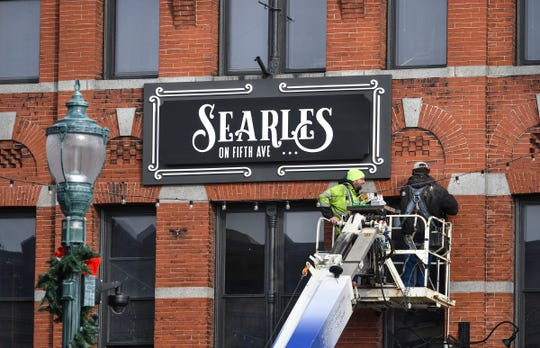 Ben Arneson and Adrion Jennen of Indigo Signworks install a new sign for Searles on Fifth Ave. Wednesday, Nov. 20, 2019, in St. Cloud. They earlier removed the former D.B. Searle's sign from the building. The old sign is being sold through a sealed-bid auction.