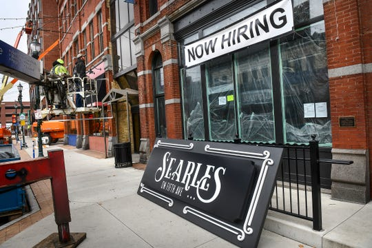 Workers prepare to install a sign for the coming bar and restaurant Searles on Fifth Ave. Wednesday, Nov. 20, 2019.