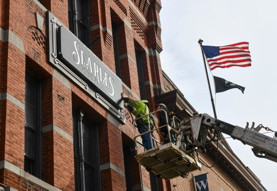 Ben Arneson and Adrion Jennen of Indigo Signworks install a new sign for Searles on Fifth Ave. Wednesday, Nov. 20, 2019, in St. Cloud.