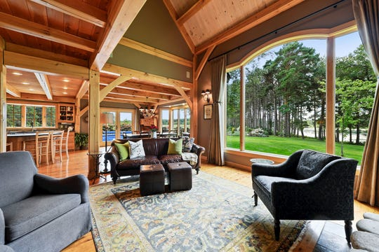 The living room features vaulted ceilings and an extensive picture window that looks out to the water.