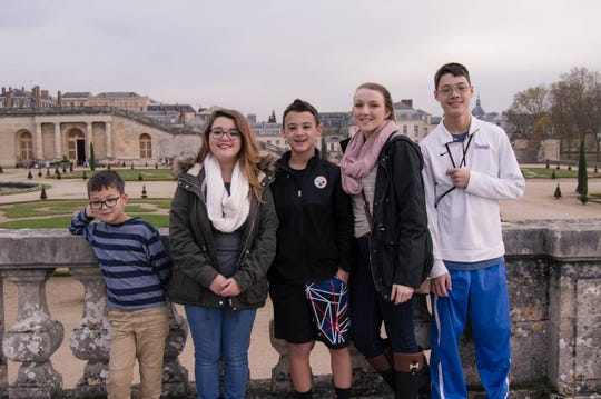 Alicia Devine, second from right, poses for a photo with her half siblings Danny, Ashley, Alex, and Anthony Wong while at the Palace of Versailles.