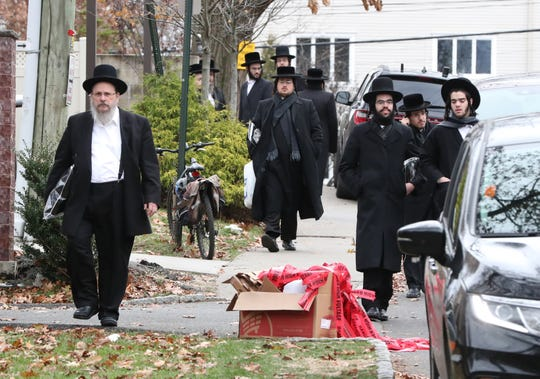People walk by the scene of a stabbing on Howard Dr. In Monsey Nov. 20, 2019.