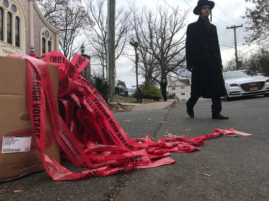 "A pedestrian walks near red ""danger"" tape near the scene of an attack on a man who police said  was headed to morning prayers on Howard Drive in Monsey on Nov. 20, 2019."