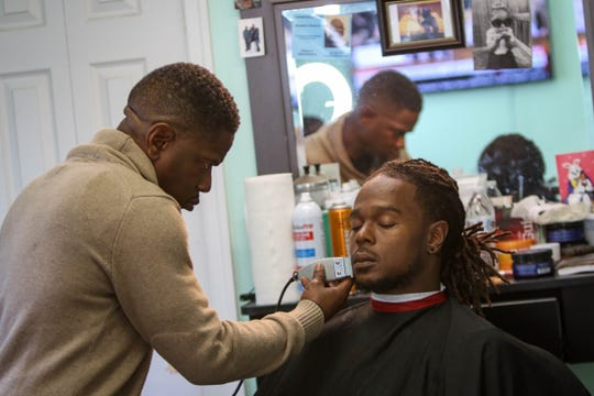 Edward Harrison gives his son, Edward Harrison Jr., a cut at Pryme Styles and Cuts, the barbershop and cafe he owns in Wilmington.