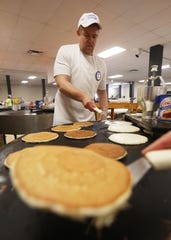 Dave Stewart flips pancakes during Sertoma Pancake Day in Zanesville Wednesday. The annual event is a fundraiser for Sertomas various charitable causes.
