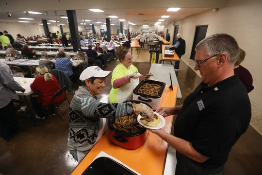 Theresa Jacolenne serves sausage to Darin Alexander of Century National Bank during Sertoma Pancake Day at Secrest Auditorium in Zanesville on Wednesday.