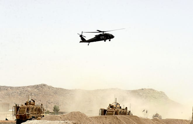 "In this Wednesday, Aug. 2, 2017 file photo, A US military helicopter flies over the site of a suicide bomb that struck a NATO convoy in Kandahar south of Kabul, Afghanistan. In an ""open letter"" to U.S. President Donald Trump, Afghanistan's Taliban on Tuesday reiterated their call for a withdrawal of troops to end the protracted war."