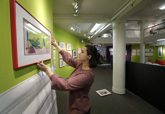 "Assistant curator Ann Weuve centers an art piece from the 1966 television special ""How the Grinch Stole Christmas!"" Thursday at the Trout Museum of Art in Appleton."