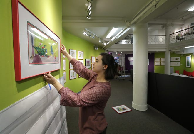 """Assistant curator Ann Weuve centers an art piece from the 1966 television special """"How the Grinch Stole Christmas!"""" Thursday at the Trout Museum of Art in Appleton."""