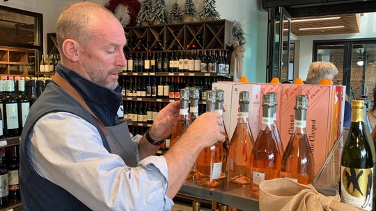 Donnie Woodham, floor manager at Bottles by Sickles. arranges wine on the shelves at Sickles' new wine and beer shop.