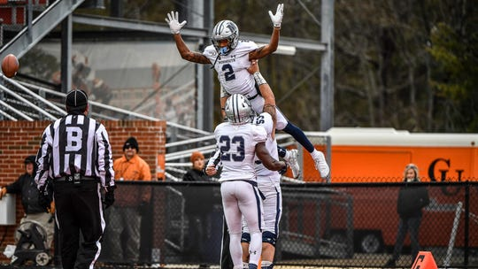 Monmouth players lift receiver Lonnie Moore (2) after his touchdown catch against Campbell during the Hawks' 47-10 victory.