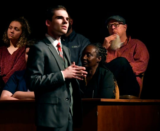 """Reporter-News columnist Greg Jaklewicz listens to the defense attorney (student actgor Nathan Lowe) during Wednesday's performance of """"The Night of January 16th"""" at Van Ellis Theatre at Hardin-Simmons University."""