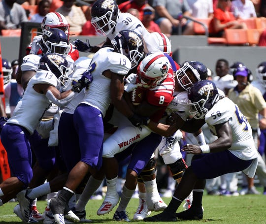 Sep 7, 2019; Raleigh, NC, USA; North Carolina State Wolfpack running back Ricky Person Jr. (8) is tackled by numerous Western Carolina Catamounts players during the first half at Carter-Finley Stadium. Mandatory Credit: Rob Kinnan-USA TODAY Sports