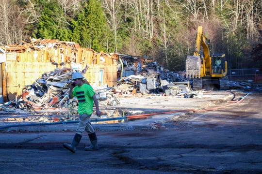 A construction worker walks in front of Seabeck Elementary School as demolition takes place. Demolition started this week and will continue through January.