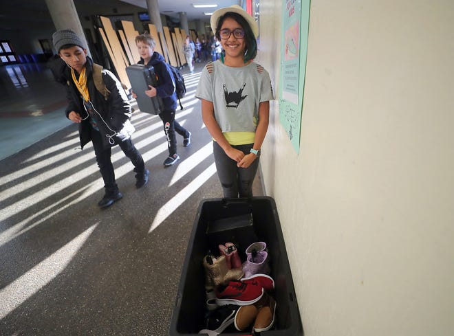 """Ridgetop Middle School seventh-grader Kai Joseph stands in the hallway and talks about collecting new shoes for foster kids as part of her """"New Shoes for Cool Kids"""" event. Joseph's goal was to collect 313 pairs of shoes during the drive."""