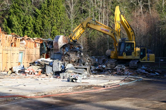 An excavator breaks through Seabeck Elementary on Tuesday. The school, which has been closed since 2007, is in the process of being torn down. The school's gym, built in 1990, will remain for community use.