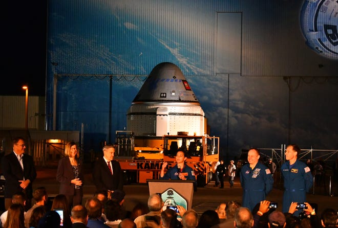 Astronaut Nicole Mann addresses the audience, standing with John Mulholland, Kathy Lueders, Bob Cabana, fellow astronauts Mike Finke and Chris Ferguson. Boeing's Starliner spacecraft rolled out of Space Florida's Commercial Crew and Cargo Processing Facility (C3PF) before dawn at Kennedy Space Center. The spaceship is scheduled to fly in December.