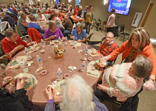 Miki Zeigler serves visitors an early Thanksgiving dinner Thursday afternoon at Trillium Event Center.
