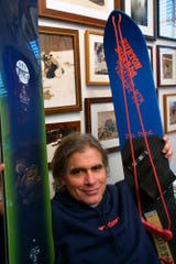 In this March 8, 2002, file photo, Jake Burton Carpenter, owner of Burton Snowboards, shows an early model, right, and one of the newer snowboards, left, in his office in Burlington, Vt. Carpenter, the innovator who brought the snowboard to the masses and helped turn the sport into a billion-dollar business, has died after a recurring bout with cancer. He was 65. Officials from the company he founded, Burton Snowboards, told The Associated Press of his death Thursday, Nov. 21, 2019.