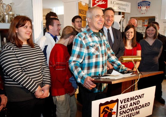 In this March 8, 2012, file photo, Jake Burton Carpenter, the creator of Burton Snowboards, center, speaks during a bill signing with Gov. Peter Shumlin, to the right of Burton, in Stowe, Vt.