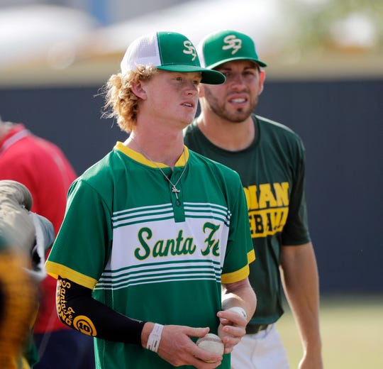Santa Fe High School baseball player Rome Shubert waits with teammates before a baseball game against Kingwood Park High School in Deer Park, Texas, Saturday, May 19, 2018. A gunman opened fire inside Santa Fe High School Friday, May 18, 2018, killing at least 10 people. Shubert was hit in the neck during the shooting. (AP Photo/David J. Phillip)