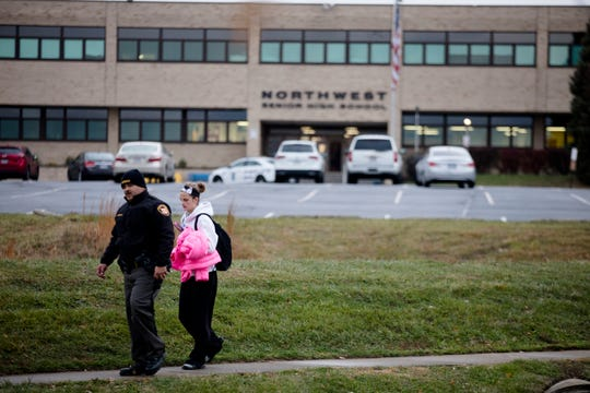 A Hamilton County Sheriff's deputy walks a Northwest High School student home while other police gather information about a shooting on Newmarket Drive, a block from Northwest High School in Colerain Township on Thursday, Nov. 21, 2019.