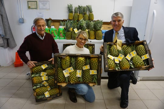 Leslie Parikh (center) and Richard Cushing (right), senior partners at Gebhardt & Kiefer Law Offices, present the firm's donation of 135 pineapples, 135 bottles of laundry detergent, and 135 bags of sugar to Joe McGrath, director of Operations/VP of the Delaware Valley Food Pantry (left).