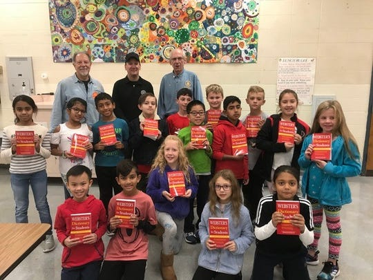 "Amsterdam Elementary School students, and perhaps future Rotarians, show off their new dictionaries compliments of the Rotary Club of Hillsborough.  The children were asked to look up the word ""charity,"" which sparked a lively discussion of community service. The club donates new dictionaries each year to all Hillsborough and Manville third-graders. Rotarians Rich Salem, Mike Dudzinski and Jim Machut were on hand to deliver the books and talk with the children."