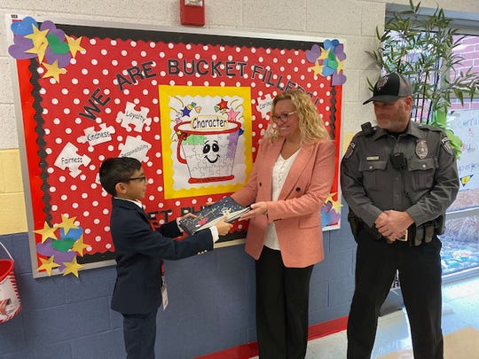 Pictured here is third-grader, Shravan Patel, serving as the Gratitude Ambassador from Whitehouse School, as he delivers tokens of appreciation on behalf of the school. Laura Simon, the Board of Education President for the Readington Township School District, and Special Officer John Harris of the Readington Township Police Department, accepted the messages tailored to members of their groups.
