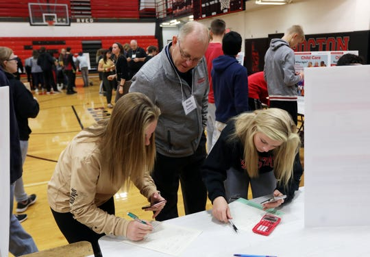 State Farm Insurance agent Doug Marmie talks about the cost of car insurance with Coshocton High School students Keeley Murray, right, and Olivia Blust during the Real Life Real Money event at the school.